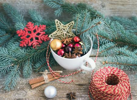 Kerstmis (Nieuwjaar) decoratie set: een beker vol colrful kerstboom speelgoed, kaneelstokjes en een decoratie touw op een rustieke houten achtergrond. Selectieve aandacht Stockfoto