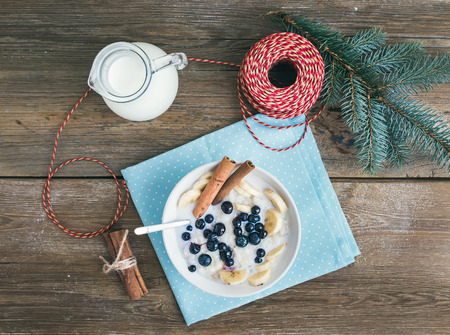 top year: Rice porridge with milk, cinamon, banana and blueberry with Christmas (New Year) decorations on a rustic wood background. Top view
