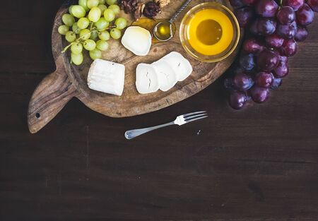 queso de cabra: Goat brie cheese with fresh greapes and honey on a rustic wooden board over a dark wood background with a copy space