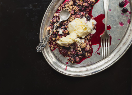 teaspoon: Baked oatmeal with berries and vanilla ice-cream with a tea-spoon and a fork on a silver dish on dark over a black metal background