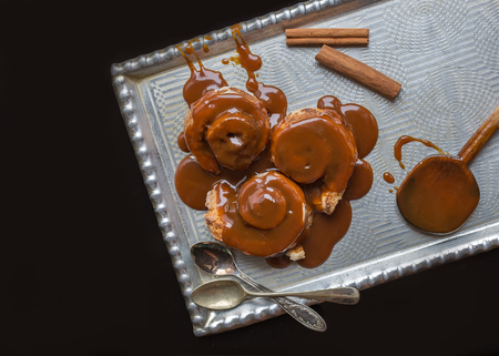 silver tray: Cinnamon rolls with warm caramel topping and cinnamon sticks on a silver tray with tea-spoons over a black background