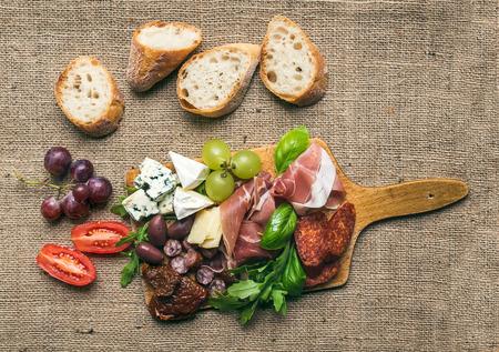 jamon y queso: Set de vino que consiste en carne ahumada, salchichas, varios tipos de queso, uvas verdes y rojas, cereza, tomates, aceitunas, hojas de albahaca verde, rúcula, tomates secos y rebanadas de pan sobre tabla de madera arustic sobre el fondo de la arpillera