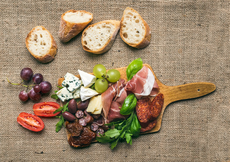 Wine set consisting of smoked meat, sausages, various cheese kinds, green and red grapes, cherry-tomatoes, olives, green basil leaves, ruccola, dried tomatoes and baguette slices on arustic wood board over the hessian background