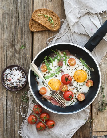 Pan of fried eggs, bacon and cherry-tomatoes with bread on rustic wood table surface, top view Stock Photo