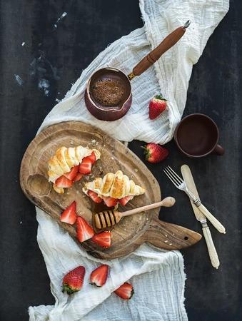 Breakfast set. Freshly baked croissants with strawberries, mascarpone, honey and coffee on rustic wooden board over dark grunge backdrop, top view photo