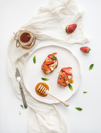 traditionally french: French toasts with strawberry, cream cheese, honey and mint on light ceramic plate over white backdrop, top view Stock Photo