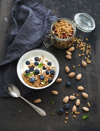Healthy breakfast. Oat granola with fresh blueberries, almond, yogurt and mint in a rustic metal bowl over dark grunge surface photo