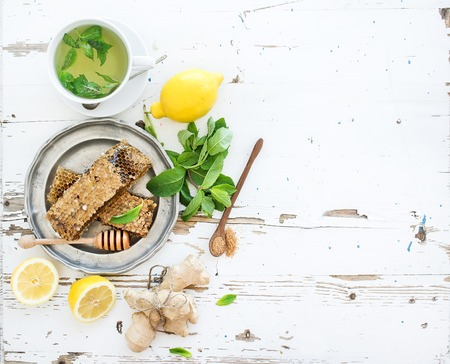 ginger tea: A cup of herbal tea with fresh mint, honey, lemon, ginger on rustic white wooden background. Top view, copy space