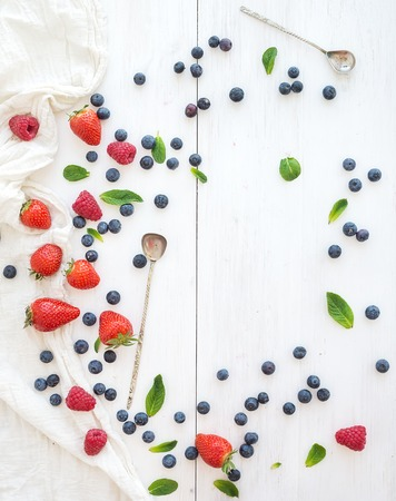 Berry frame with copy space on right. Strawberries, raspberries, blueberries and mint leaves, white wooden background, top view photo