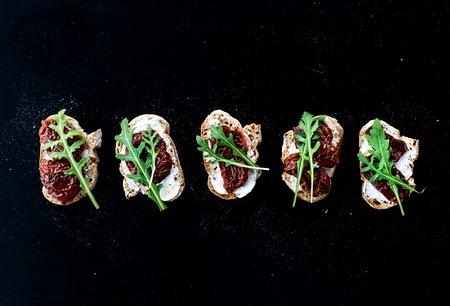pan y vino: Bruschettas con tomates secos, r�cula y carne ahumada sobre un fondo negro. Vista superior