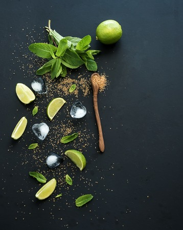 alcool: Ingrédients pour mojito. Menthe fraîche, citron vert, glace, sucre sur fond noir. Vue d'en haut, copie, espace