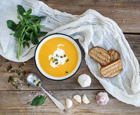 Pumpkin soup with cream, seeds, bread and fresh basil in metal plate on rustic wood background. Top view