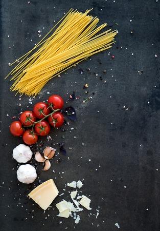 食品のフレーム。パスタの食材。チェリー トマト、スパゲティ、ニンニク、バジル、パルメザン チーズとスパイス暗いグランジ背景、コピー領域の