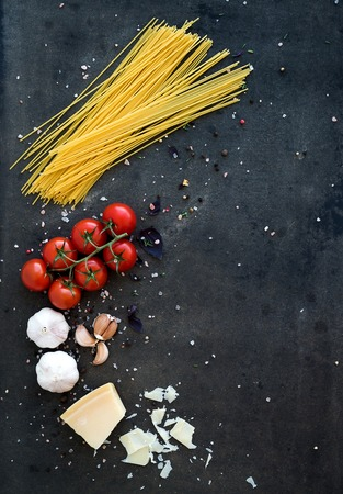 Food frame. Pasta ingredients. Cherry-tomatoes, spaghetti pasta, garlic, basil, parmesan and spices on dark grunge backdrop, copy space, top view