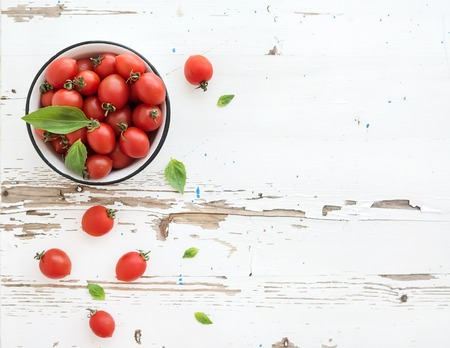 tomate cherry: Tomates cherry en un recipiente de metal y hojas de albahaca fresca sobre fondo de madera rústica blanco, vista desde arriba, copia espacio Foto de archivo