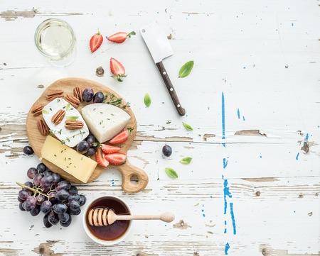 merienda: Selección de aperitivo de queso o un aperitivo de vino set. Variedad de quesos, uvas, nueces pecan, fresa y miel sobre tabla de madera redonda sobre el contexto blanco rústico, vista desde arriba, copia spce Foto de archivo