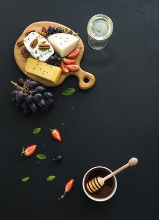 Drinking wine: Cheese appetizer selection or whine snack set. Variety of cheese, grapes, pecan nuts, strawberry and honey on round wooden board over black backdrop, top view, copy space
