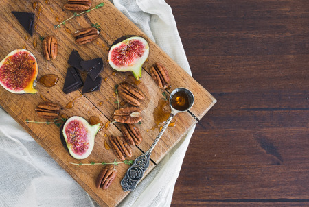 pekan: Fresh figs and pekan nuts with honey on a wooden board and white tissue