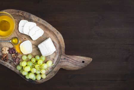 board desk: Goat brie cheese with fresh greapes, walnuts and honey on a rustic wooden board over a dark wood background with a copy space. Top view