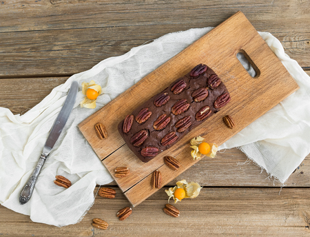 ground cherry: Pecan brownie cake with ground cherry on a wooden board