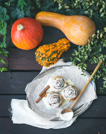 white backing: Cinnamon pumpkin buns with creamy cheese icing and ripe pumpkins over a dark wood background