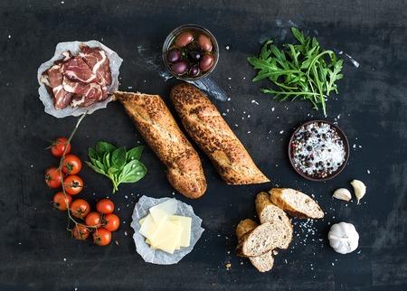 검은 grunge 배경 위에 훈제 고기, 바게트, 바질, 즐기기, 올리브, 체리 토마토, 파르 메산 치즈를 치즈, 마늘, 향신료와 샌드위치 재료입니다. 평면도