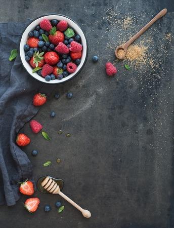 fresa: Fresas, frambuesas, arándanos y hojas de menta, miel, azúcar de caña, fondo oscuro del grunge, vista superior, copia espacio
