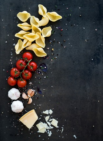 Cherry-tomatoes, pasta, garlic, basil, parmesan and spices on dark grunge backdrop, copy space, top view