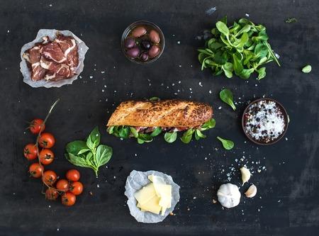 燻製肉、バゲット、バジル、ルッコラ、オリーブ、チェリー トマト、パルメザン チーズ、ニンニクとスパイス黒グランジ背景の上でサンドイッチの