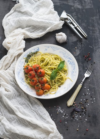 Pasta spaghetti with pesto sauce, basil, baked cherry-tomatoes on rustic wooden dark table, top view, copy space photo