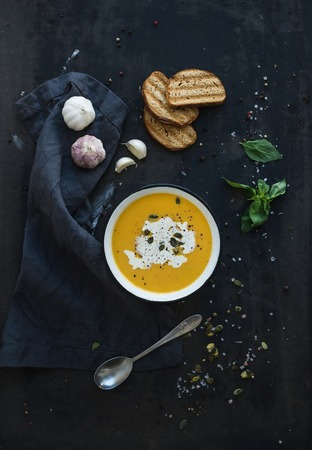 black dish: Pumpkin soup with cream, seeds, bread and fresh basil in rustic metal plate on grunge black background. Top view Stock Photo