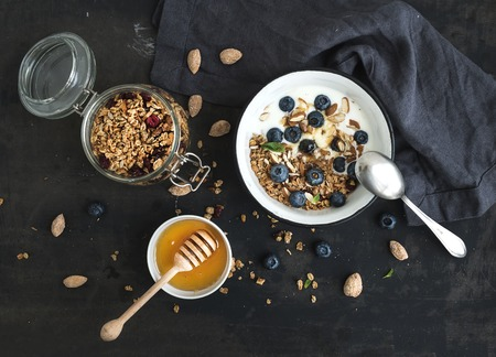 Oat granola with fresh blueberries, almond, yogurt and mint in a rustic metal bowl over dark grunge surface photo