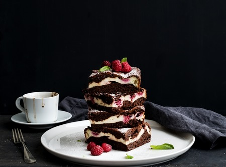 Brownies-cheesecake tower with raspberries on white ceramic plate photo