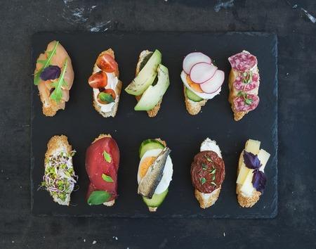 미니 샌드위치 세트입니다. 검은 배경에 작은 샌드위치의 다양한 평면도 스톡 콘텐츠