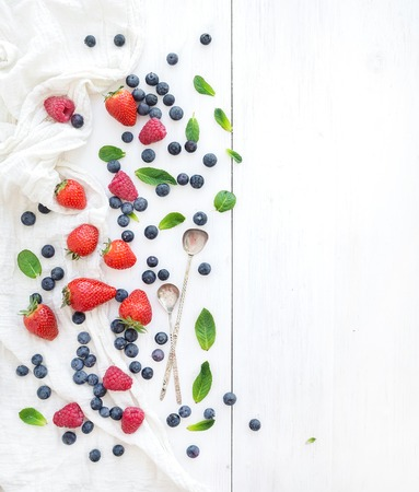 Strawberries, raspberries, blueberries and mint leaves, white wooden background, top view photo