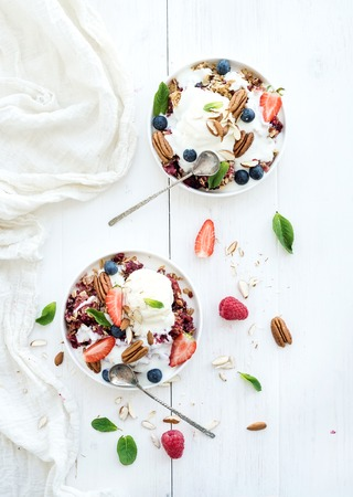 Healthy breakfast. Berry crumble with fresh blueberries, raspberries, strawberries, almond, walnuts, pecans, yogurt, and mint in ceramic plates over white wooden surface, top view