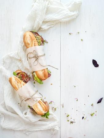 bocadillo: Sandwiches con carne, verduras y hierbas frescas sobre fondo de madera blanco, vista desde arriba, copia espacio Foto de archivo
