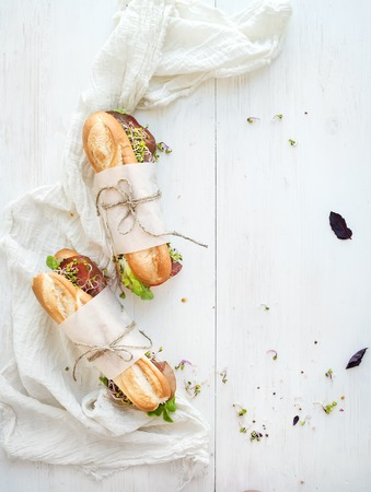 Sandwiches with beef, fresh vegetables and herbs over white wood backdrop, top view, copy space