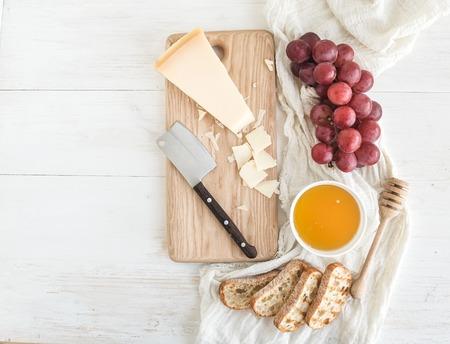 パルメザン チーズとブドウ、蜂蜜、パンは素朴な白背景に木製のまな板にスライスします。コピー スペース平面図