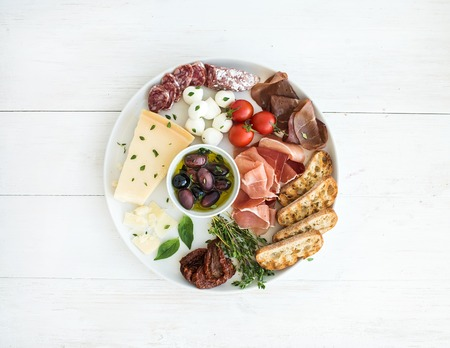 antipasto: Cherry-tomatoes, parmesan cheese, meat variety, bread slices, dried tomatoes, olives and basil on round ceramic plate over white wood backdrop, top view Stock Photo
