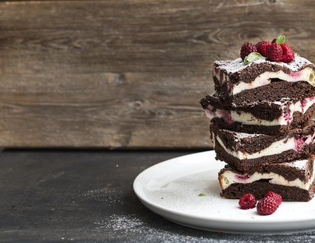 Brownies-cheesecake tower with raspberries on white ceramic plate, wooden backdrop, copy space