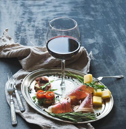bread and wine: Establece aperitivo Vino. Copa de vino tinto, vajilla vintage, brushetta con la cereza, tomates secos, r�cula, parmesano, carne ahumada en bandeja de plata sobre la superficie del grunge r�stico. Acercamiento