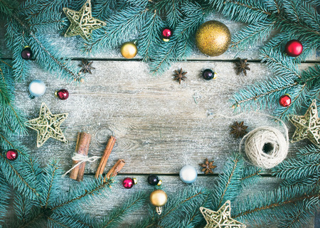 surface view: Christmas (New Year) decoration background: fur-tree branches, golden, red and silver glass balls, golden glittering toy stars, cinnamon sticks and anise stars on a rough wooden desk with a copy space