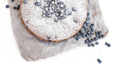 sugar powder: Blueberry cake with fresh bluberries and sugar powder on a beige fabric over a white background
