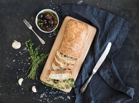 comida italiana: Pan ciabatta italiana cortar en rodajas sobre tabla de cortar madera con hierbas, ajo y aceitunas más grunge oscuro telón de fondo, vista desde arriba