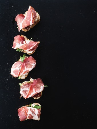 antipasto platter: Bruschettas with prosciutto smoked meat, dried tomatoes and arugula over  black backdrop, top view, copy space Stock Photo
