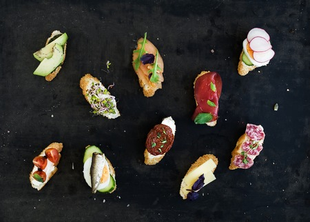 Mini sandwich set. Variety of small sandwiches on black backdrop, top view