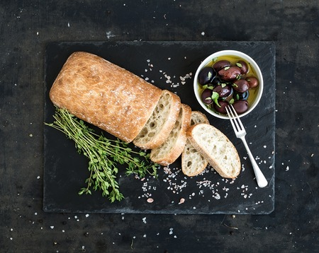Italian ciabatta bread cut in slices on wooden chopping board with herbs, garlic and olives over dark grunge backdrop, top view Imagens