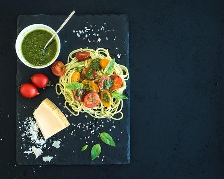 ペストソース、ローストしたチェリー トマト、新鮮なバジル、暗いグランジ背景にボードを提供する黒い石にパルメザン チーズのスパゲッティ。コ