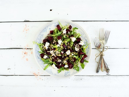 Beetroot salad with arugula, feta cheese and pumpkin seeds in vintage plate over white rustic wooden background, top view,